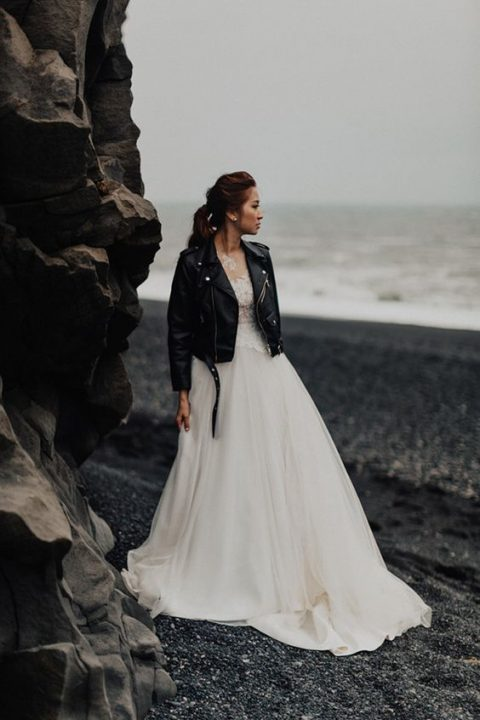 a chic A-line wedding dress with a lace bodice and a black moto jacket