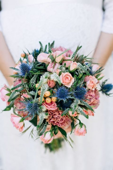 a colorful bouquet with pink blooms, blue thistles and greenery