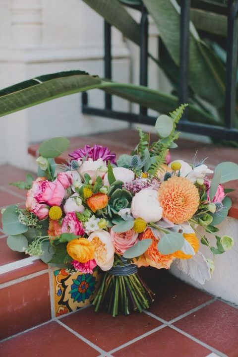 a colorful bouquet with pink, yellow and orange blooms and greenery