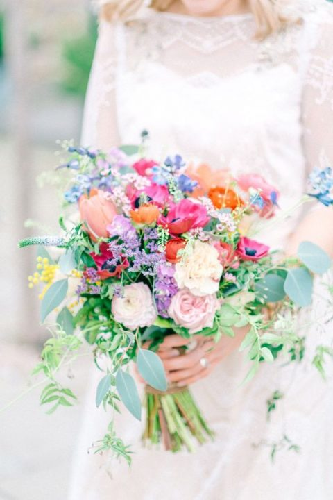 a colorful bouquet with red, fuchsia and orange blooms and blush and ivory blooms