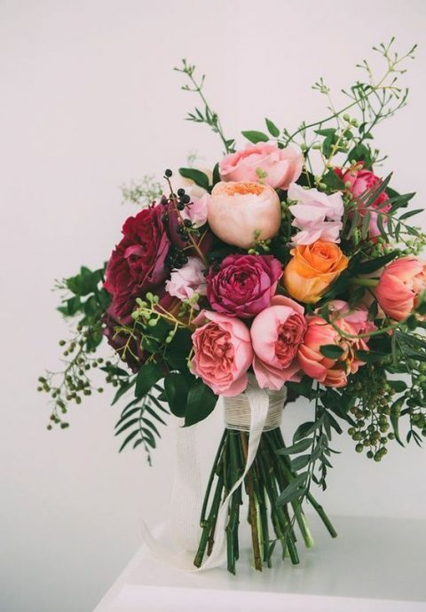 a cute summer bouquet with blush, pink, fuchsia and orange blooms plus greenery