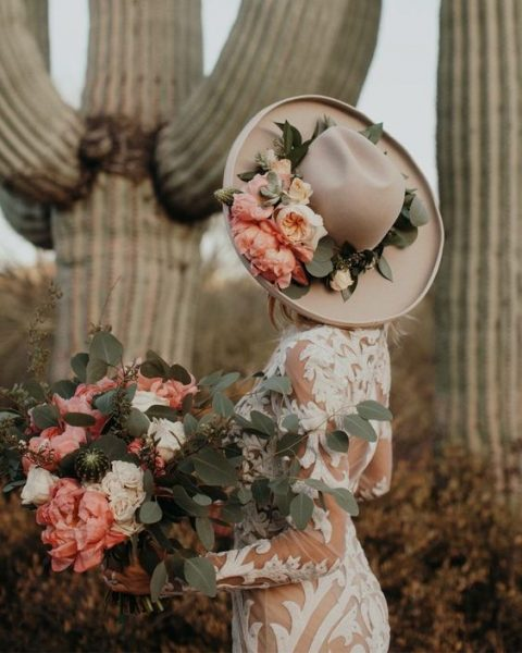 a gorgeous hat decorated with leaves and pink blooms