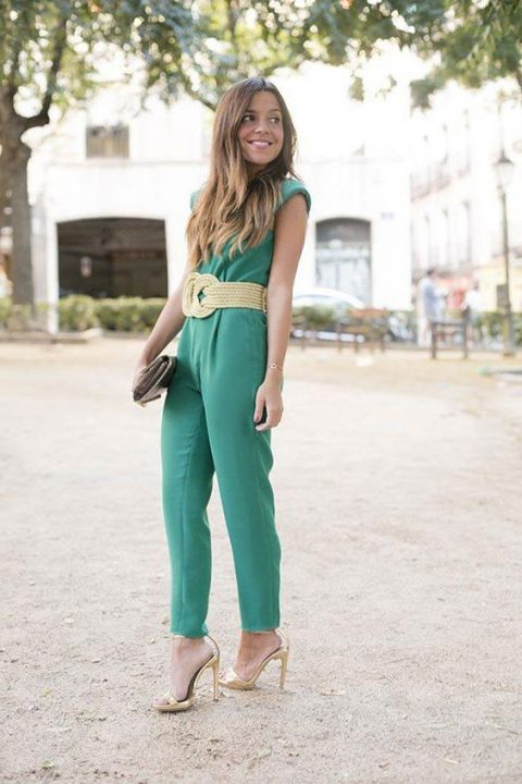 a green sleeveless jumpsuit with a woven belt and metallic shoes