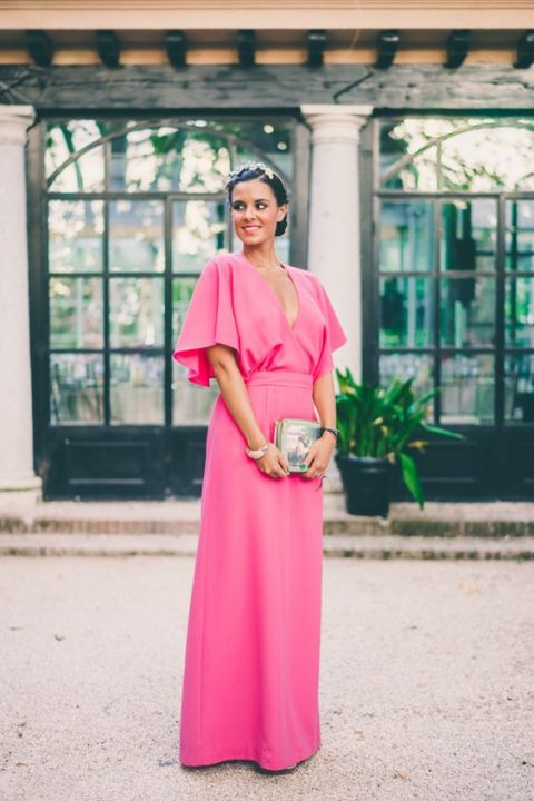 a hot pink maxi dress with comfy ruffled sleeves, a headpiece and a tropical print clutch