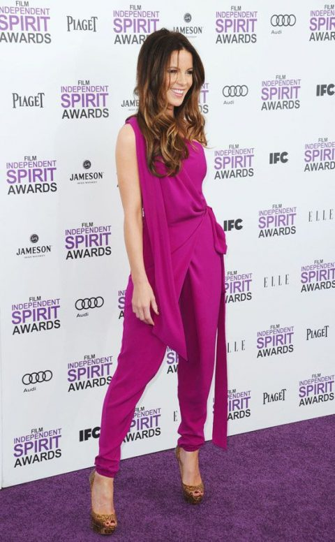 a hot pink one shoulder jumpsuit with a sash, printed heels and a metallic clutch