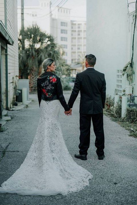 a lace mermaid wedding dress with a handpainted leather jacket on