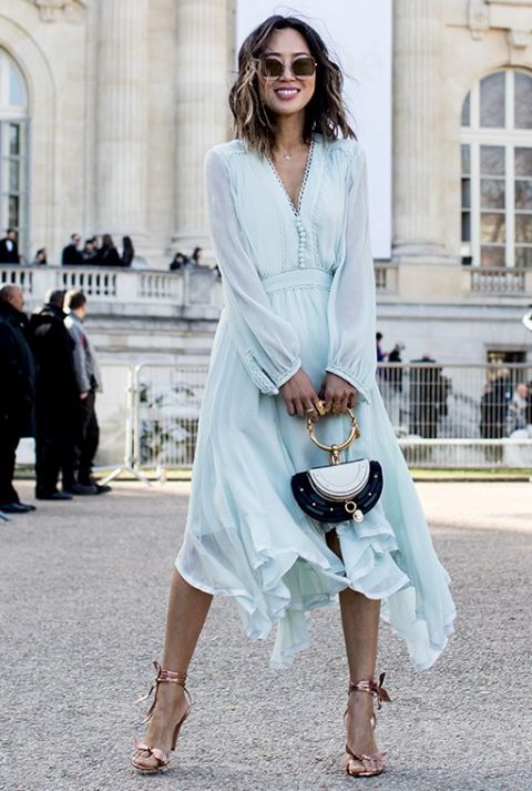 a light blue flowy dress with a V-neckline, buttons and ruffled skirt, pink shoes and an eye-catchy clutch