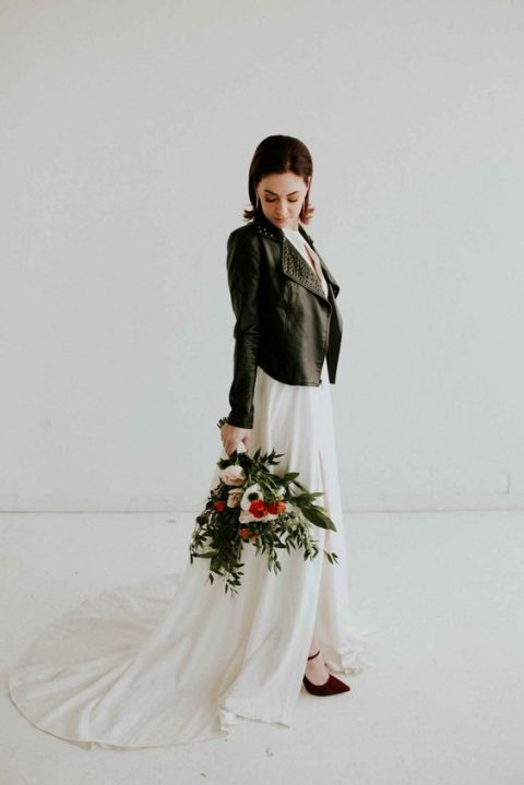 a modern bridal look with a chic front slit with a train and a black studded leather jacket
