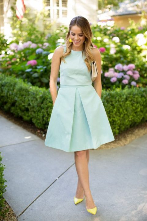 a modest mint-colored two piece dress, a creamy clutch and bold yellow shoes and earrings