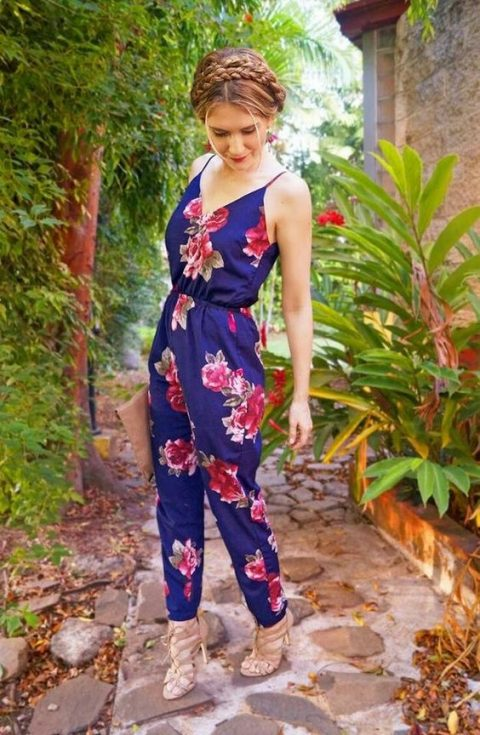 a navy jumpsuit with bold floral prints, nude strappy heels and a braided updo