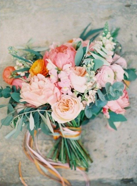 a peachy pink, orange wedding bouquet with plenty of greenery and ribbons