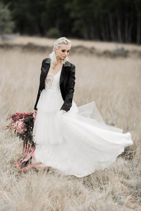 a romantic princess A-line wedding dress with a black leather studded jacket on