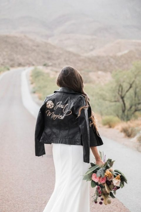 a sheath wedding dress and a white leather jacket with calligraphy