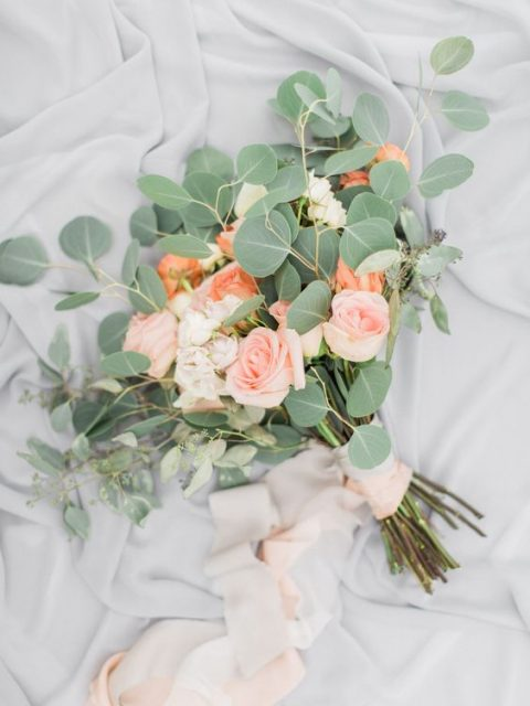 a simple wedding bouquet with blush and orange roses and eucalyptus