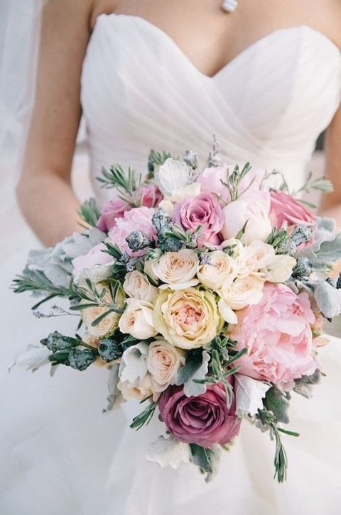 a soft pastel bouquet with ivory, blush and mauve blooms plus pale greenery