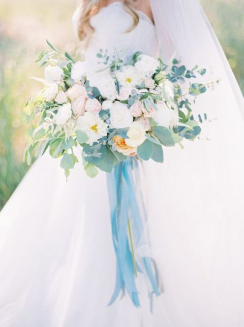 a soft pastel bouquet with white, blush blooms and greenery plus blue ribbons