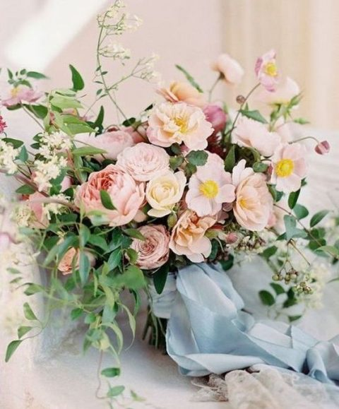 a summer bouquet with blush blooms, greenery and blue ribbons