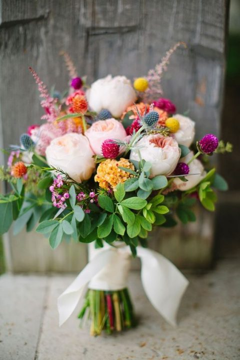 a summer bouquet with blush blooms, greenery, thistles and clover