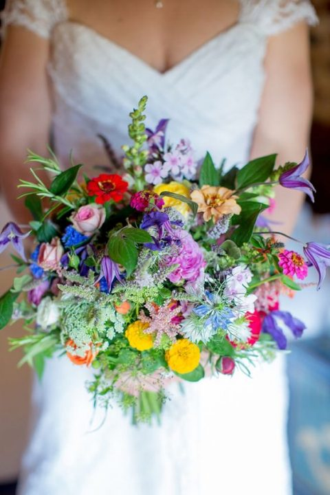 a super colroful wedding bouquet with greenery and herbs