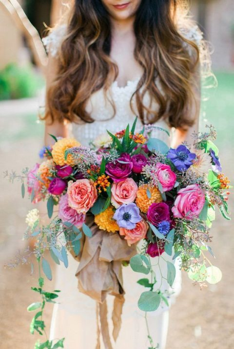 a super lush and colorful bouquet of pink, orangem purple, fuchsia blooms and greenery