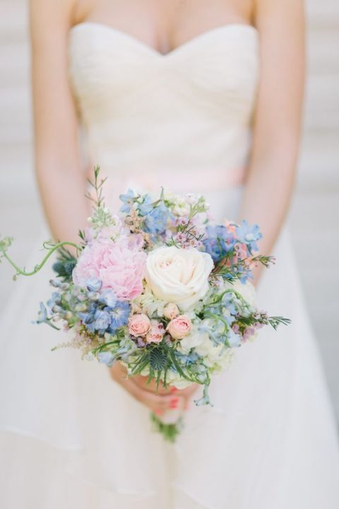 a sweet pastel bouquet with pink and blue blooms and blue thistles