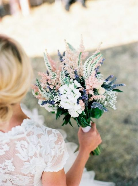 a textural bouquet with white, light pink and blue blooms and greenery