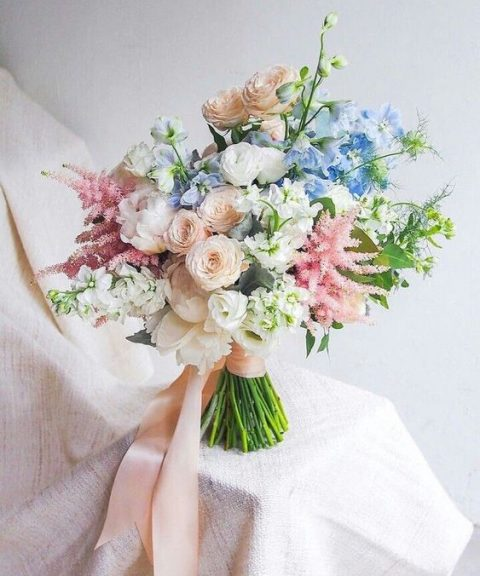 a textural summer bouquet with blush, white, blue and pink blooms and greenery plus blush ribbons