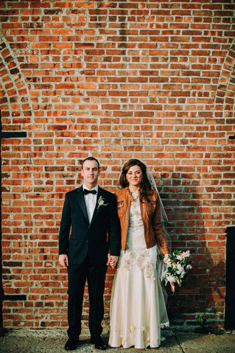 a wedding dress with lace appliques and an amber leather jacket