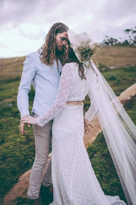 a white hat with a long veil and wildflowers for a summer boho bride