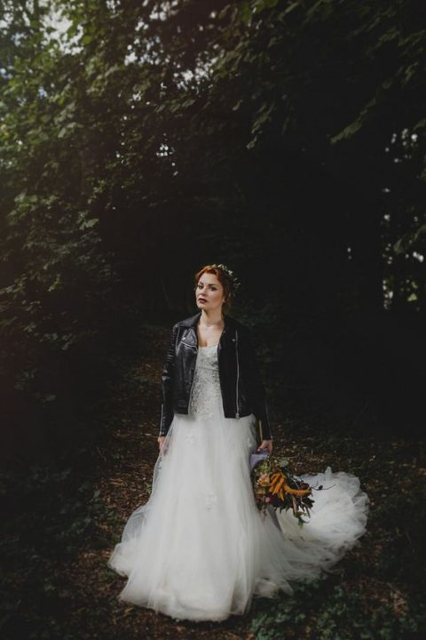 a woodland bride in a princess-style wedding dress and a black leather jacket
