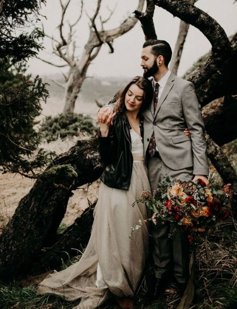 a woodland bride in an A-line lace wedding dress and a black leather jacket