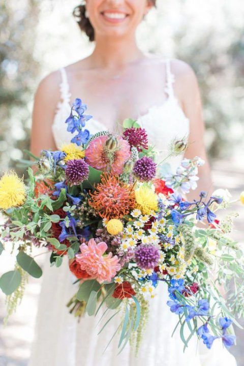 an overflowing wedding bouquet with purple, pink, blue and yellow flowers and greenery