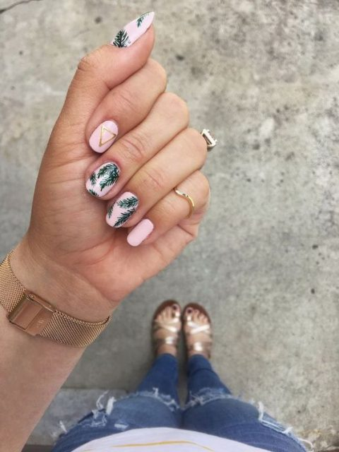 pink nails with tropical leaves and a gold triangle