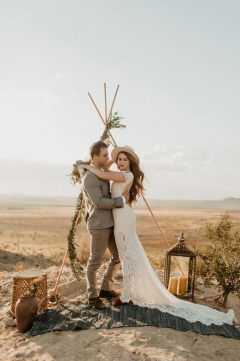 the bride rocking a boho lace dress with a cutout back and a hat
