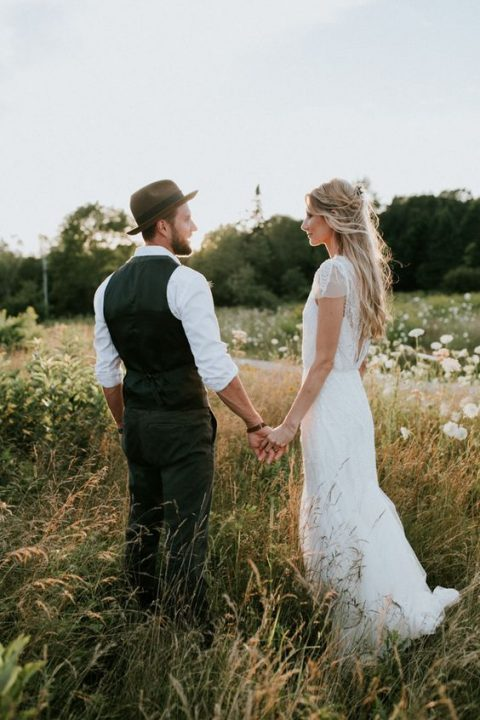 the groom in a vest, pants and a hat for a boho feel