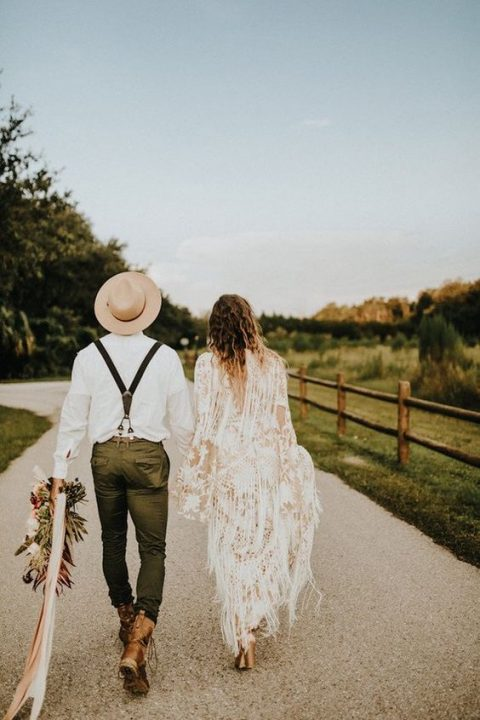 the groom in suspenders, brown boots and a hat