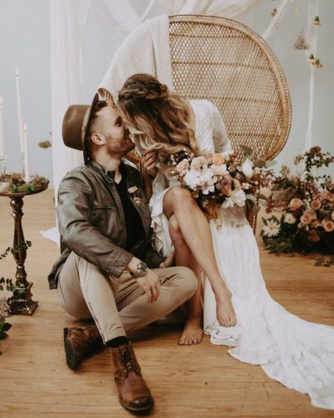 the groom rocking brown boots, a brown leather jacket and a hat