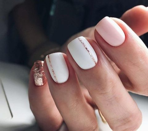 white and light pink nails with a touch of rrose gold glitter