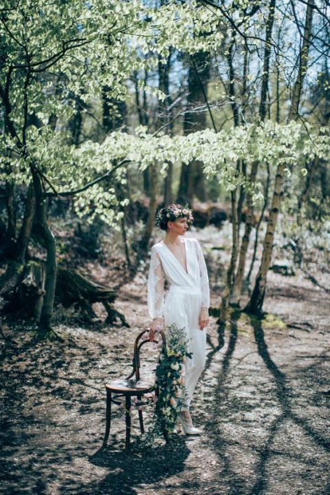a flowy white jumpsuit with long lace sleeves and a plunging neckline
