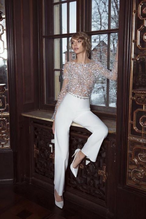 a glam jumpsuit with a fully embellished bodice and long sleeves and plain white pants and white shoes