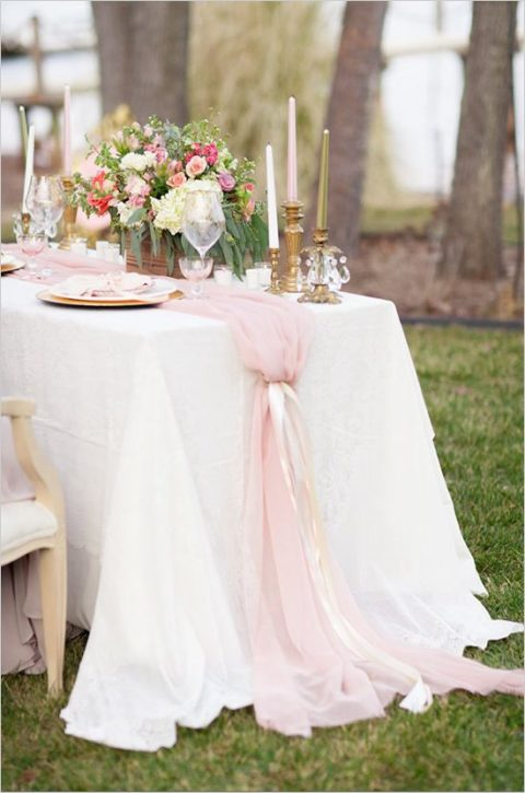 a light pink table runner with ribbons