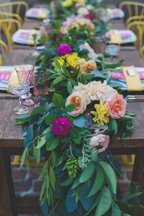 a lush and colorful greenery table runner with hot pink, blush and yellow blooms