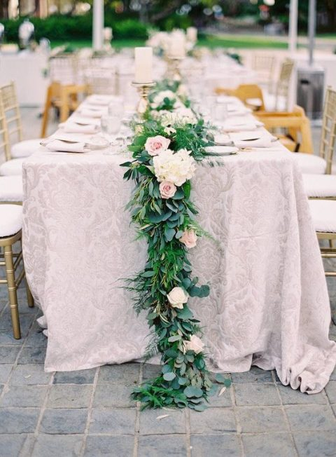 a lush greenery table runner with blush and white blooms