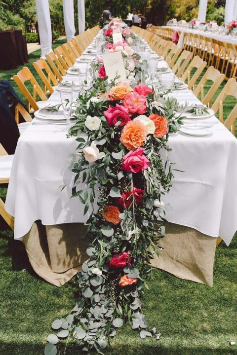 a lush greenery table runner with orange, pink and white blooms