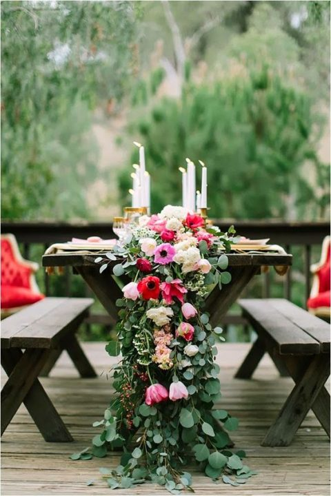 a lush greenery table runner with pink and red blooms and some candles