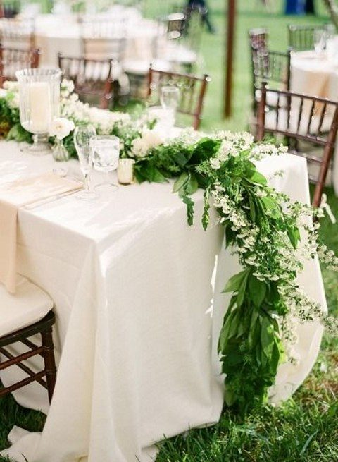 a lush greenery table runner with white flowers
