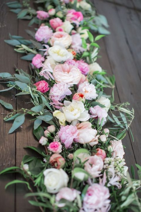 a lush wedding table runner with greenery, white, pink and blush blooms