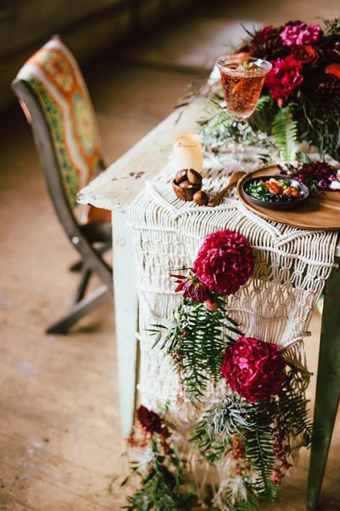 a macrame table runner with burgundy blooms and greenery