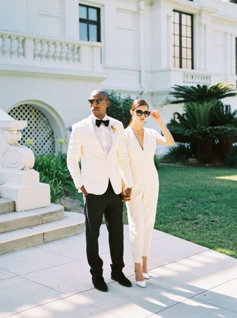 a minimalist creamy bridal jumpsuit with a deep V-neckline, a statement necklace and white heels