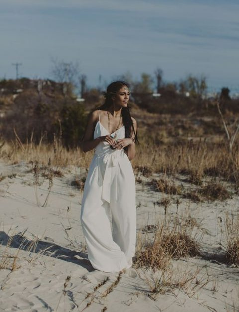 a modern ivory jumpsuit with spaghetti straps and wide leg pants plus a bow